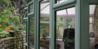 PVCu conservatory in chartwell green with top opening casement windows.