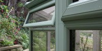 Chartwell green PVCu conservatory with top opening casement windows.