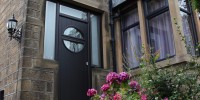 Pisa composite door in black with Abstract glass and integrated side panels and top lights.