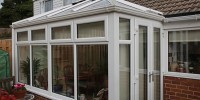 White PVCu conservatory with top opening casement windows.