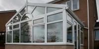 White PVCu conservatory in sunburst design with polycarbonate roof.