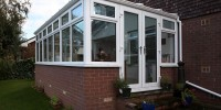 White PVCu conservatory with glass roof and French doors.